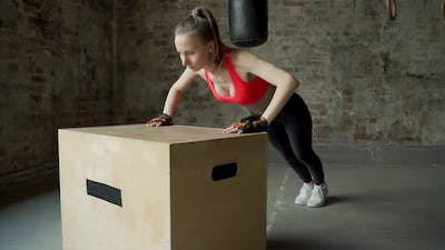 Athlete Young Woman Does Pushups on a Wooden Box in the Gym