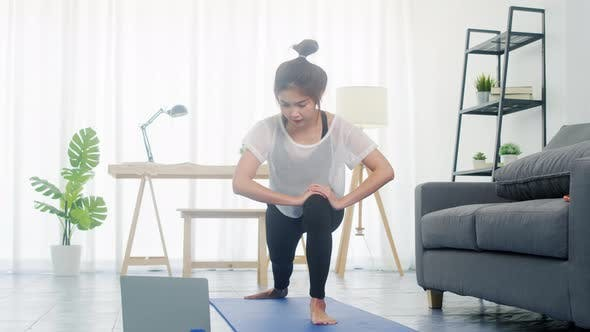 Young lady exercises doing working out and using laptop to watching yoga video tutorial at home.