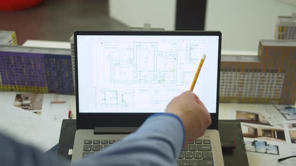Man Shows with Pencil at the Scheme of Apartement on Laptop