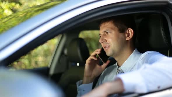 Thumbnail for Busy Businessman Communicating on Phone in Car