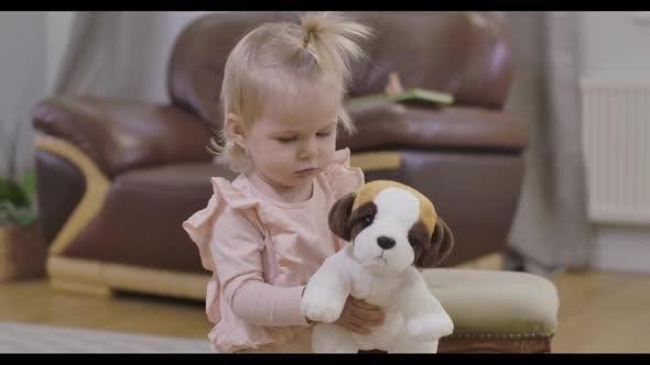 Thumbnail for Porträt von Little Beautiful Girl zu Fuß zur Kamera mit Plüschtier Hund