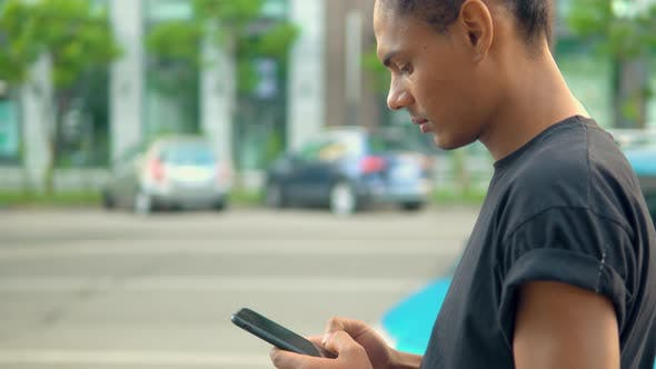 Thumbnail for Young Man Standing on the Street Using Smartphone