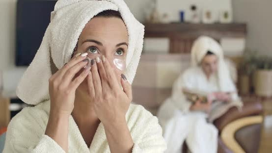 Thumbnail for Pretty Young Caucasian Woman in White Bathrobe and Hair Towel Applying Eye Gel Patches. Blurred Girl