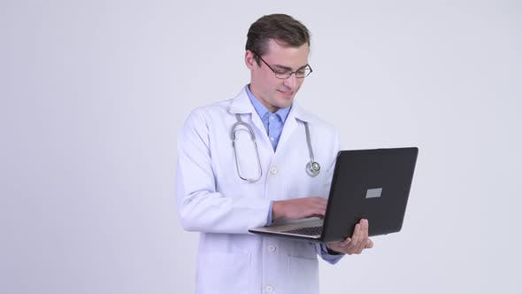 Cover Image for Young Happy Handsome Man Doctor Thinking While Using Laptop