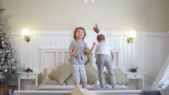 Cover Image for Little Children Jumping on Bed in Room Decorated for Christmas