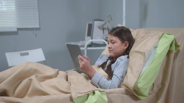 Thumbnail for Mädchen liegen auf dem Bett im Krankenhaus und spielen auf Tablet