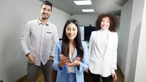 Portrait of Three Positive Multiethnic Businesspeople Waving and Talking at Camera