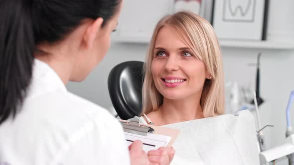 Thumbnail for Conversation between smiling woman and dentist in dentist's clinic