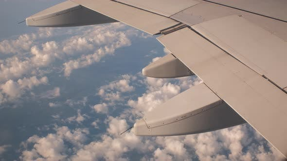 Closeup of Airplane Flying Above Fluffy Clouds