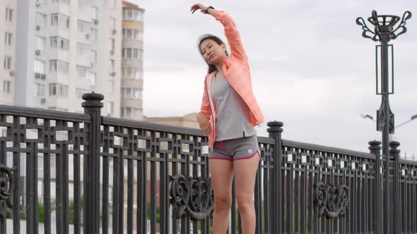 Thumbnail for Athletic Asian Woman Warming up for Morning Run in City