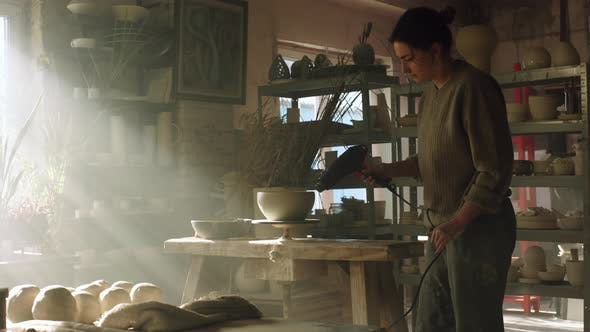 Woman Potter Is Drying Raw Clay Pot With Electric Dryer