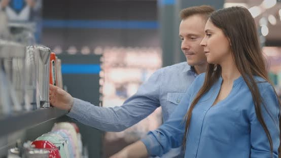 Thumbnail for A Man and Woman Hold in Their Hands an Electric Kettle in a Store Choosing Before Buying in