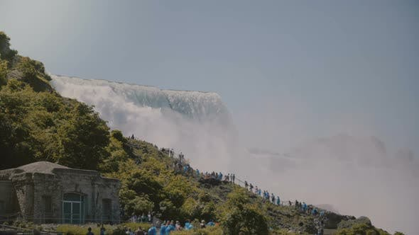 Thumbnail for Cinematic POV Shot of Tourists in Raincoats Walking Up the Ladder at Epic Beautiful Niagara Falls