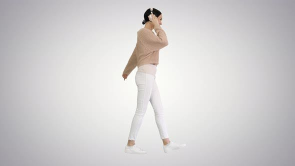 Smiling Female with Headphones Walking and Dancing To the Music on Gradient Background