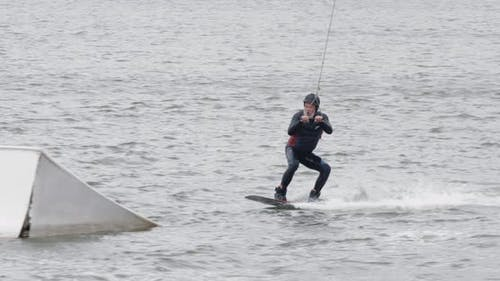 Wakeboarding in a Lake Near the Forest, Adult Man Surfs on the Water, Ride on a Wakeboarding Board