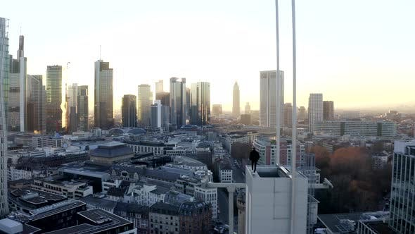 Thumbnail for AERIAL: Confident Young Man, Guy Walking on Rooftop in Skyline of Frankfurt Am Main, Germany