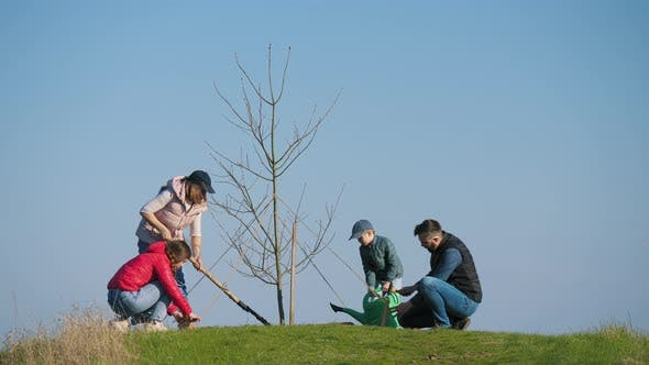 A Family with Children Caring for the Planted Tree