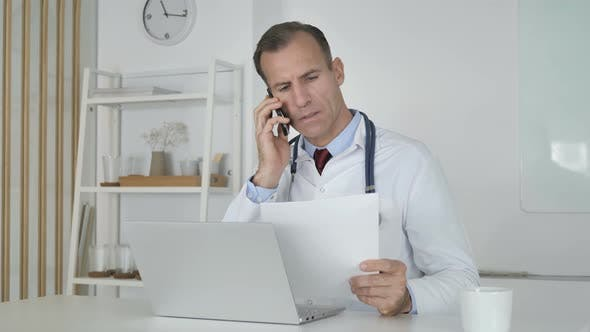 Thumbnail for Doctor Talking on Phone with Patient, Discussing Medical Report