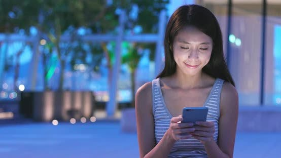 Thumbnail for Woman Looking at Mobile Phone in City at Night