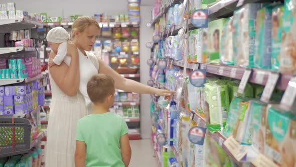 Woman with Baby and Elder Son Choosing Diapers in Supermarket