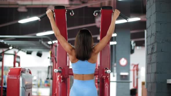 Thumbnail for Fitness Girl Training Pull Ups Exercises in Sport Machine in Gym Club. Woman Bodybuilder Pulling Up