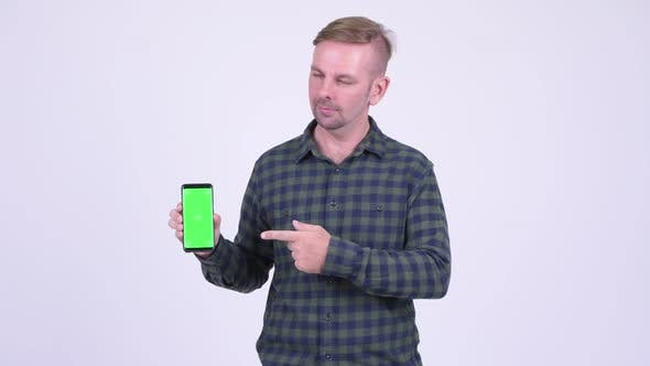 Thumbnail for Portrait of Happy Blonde Hipster Man Showing Phone and Giving Thumbs Up