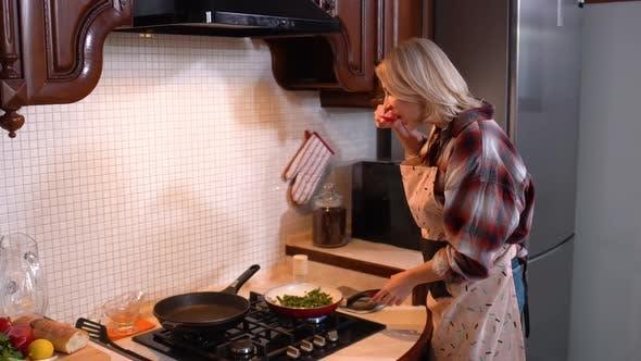 Thumbnail for Konzentrierte schöne Frau braten Spargel in der Küche zu Hause