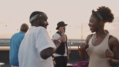 Black Man and Woman Dancing at Party on Rooftop Terrace