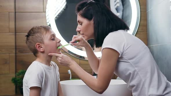 Thumbnail for Young Mother which Diligently Cleaning Her Son's Teeth in the Bathroom