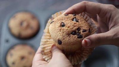 Women's Hand Breaking Muffin Cake Close Up