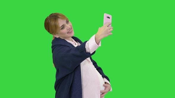 Thumbnail for Glückliche junge schwangere Frau, die Selfie auf einem grünen Bildschirm macht, Chroma Key