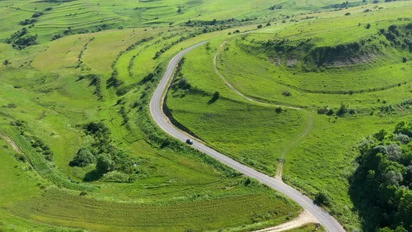 Flying Over a Car Passing on a Countryside Road Winding on a Green Meadow