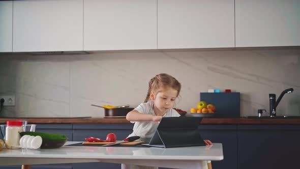 Girl Plays with Tablet at Table with Cooking Ingredients