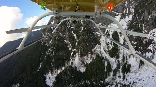 Cascade Mountain Helicopter View Flying Over Snowy Jagged Forest Ridge