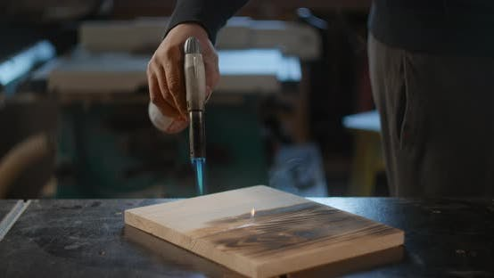 Craftsman Carpenter Scorches a Wooden Board with a Gasburner in Slow Motion Wood Aging Scorched