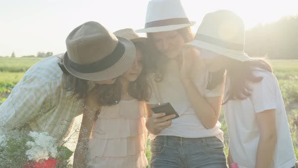 Cover Image for Happy Mother with Three Daughters Looking Into the Smartphone, Family in Nature