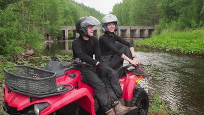 Couple Relaxing on Quad Bike in Forest