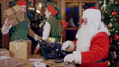 Santa and Elves with presents on Christmas decor indoor. Santa Claus is typing letter