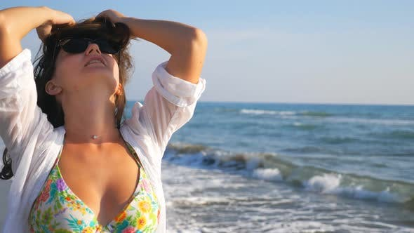 Thumbnail for Beautiful Lady in Sunglasses Smiling and Playing with Her Hair Strolling Along Coast. Portrait of