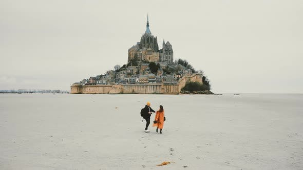 Thumbnail for Amazing Cinematic Shot, Drone Follows Happy Couple Hold Hands Walking Towards Epic Mont Saint Michel