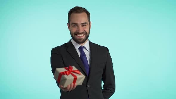 Cover Image for Handsome businessman in suit gives gift box and hands it to the camera, He is happy