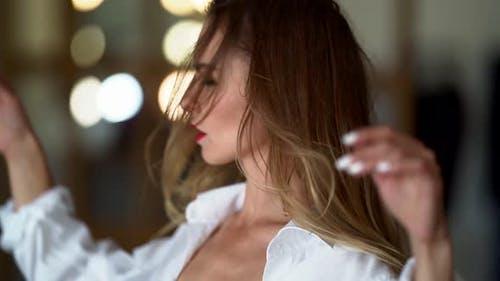 Modische schöne Frau in einem weißen Hemd posiert für die Kamera. Sie hat roten Lippenstift auf den Lippen