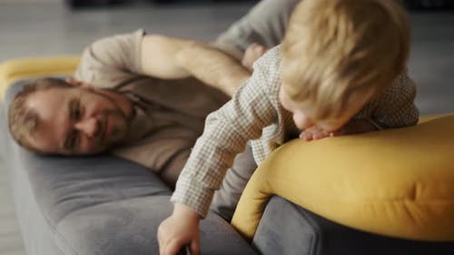 Happy Father Playing with Child on Couch at Home