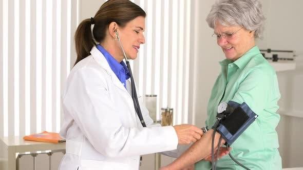 Senior doctor checking patient's blood pressure