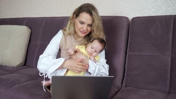 Young Woman with Toddler in Arms Typing on Laptop Concept of Female Freelancers on Maternity Leave