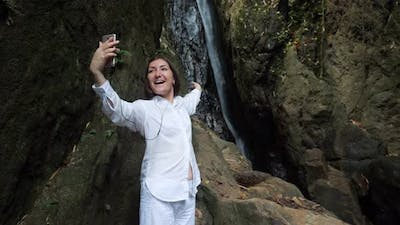 Woman in Headphones Conducts Video Call Against Waterfall
