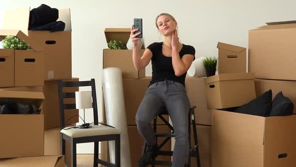Thumbnail for A Moving Woman Sits on a Chair in an Empty Apartment and Takes Selfies, Surrounded By Boxes