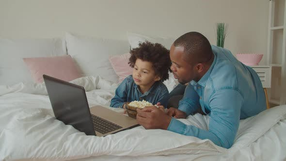 Family with Popcorn Streaming Movie Online on Bed