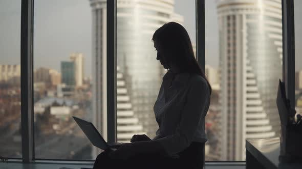 Thumbnail for Silhouette of an Attractive Girl Working on a Laptop in an Office Near the Window