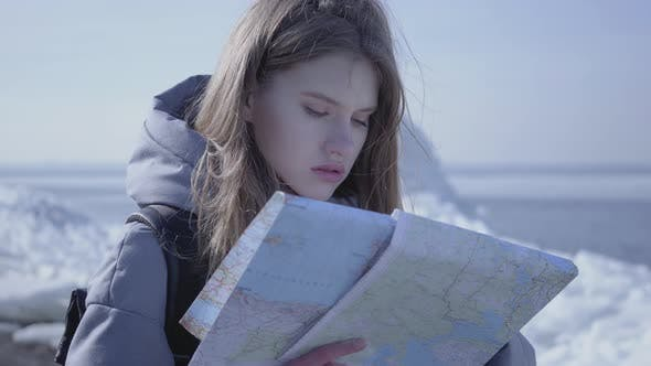 Thumbnail for Portrait of Young Blond Pretty Woman in Warm Jacket Standing on the Glacier with the Map in Hands